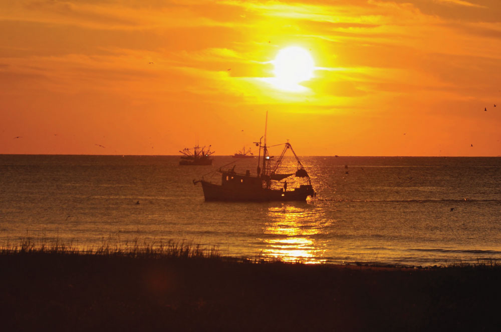 fishing boat on horizon at sunset